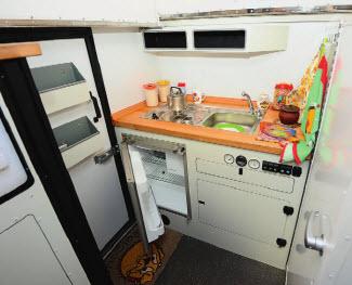 Кухня. Встроенный холодильник с морозилкой, газовая плита, раковина, контрольные приборы.